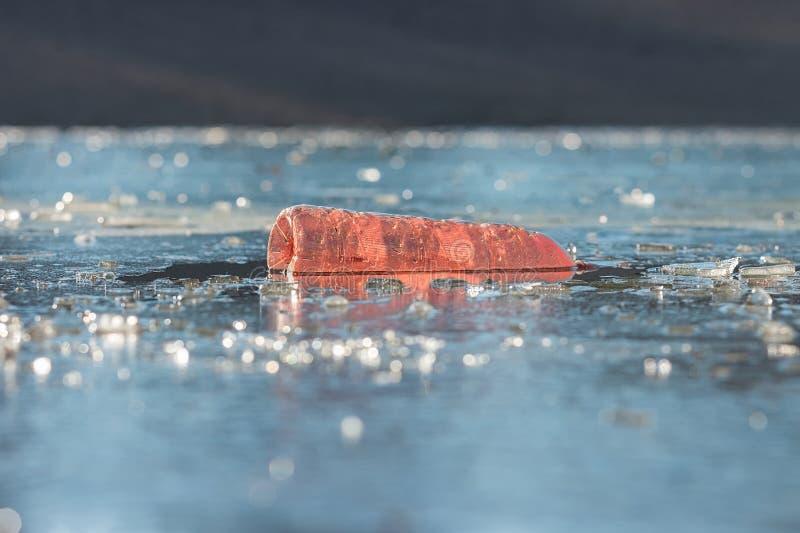 Старая пластиковая бутылка плавая на замороженное озеро стоковое фото