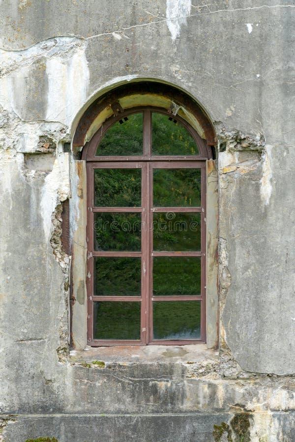 Старая поврежденная заштукатуренная кирпичная стена с окном стоковое фото rf