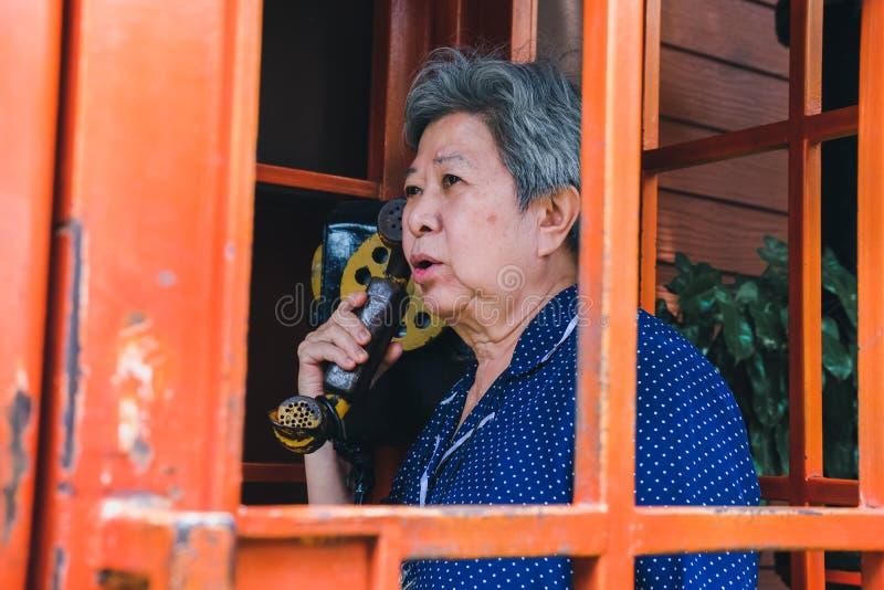 Старая пожилая старшая женщина говоря на винтажном общественном телефоне стоковая фотография