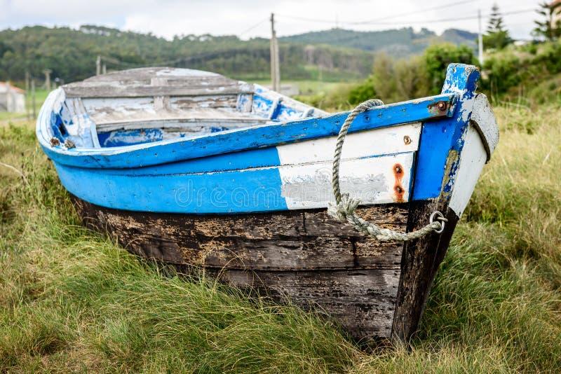 Старая покинутая деревянная рыбацкая лодка, который сели на мель на земле и траве стоковое фото