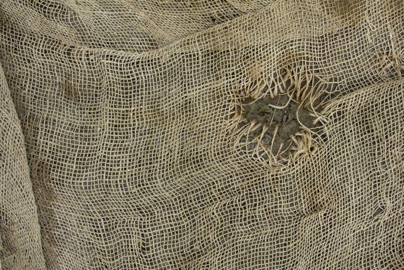 Старая поколоченная серая сетка мешковины с большим, который сгорели отверстием E стоковое изображение rf