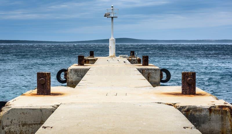 Старая пристань с маяком и штилем на море маяка стоковые изображения rf