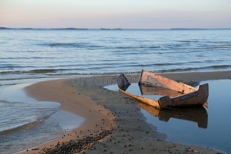Старая разрушенная рыбацкая лодка на береге вертела песка на заходе солнца стоковые фото