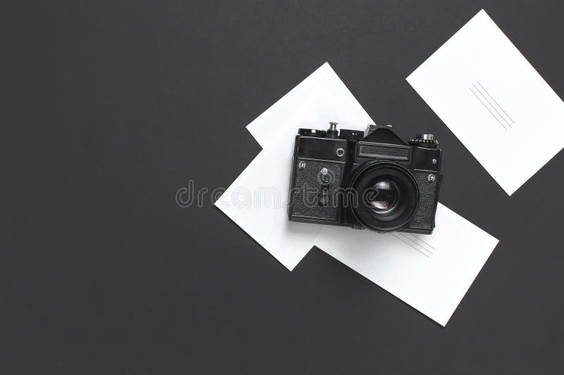 Старая ретро винтажная камера, белые пустые карты фото на черной квартире взгляда сверху предпосылки кладет с космосом экземпляра стоковые фото