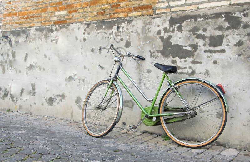 Старая ретро зеленая склонность велосипеда против стены стоковое изображение