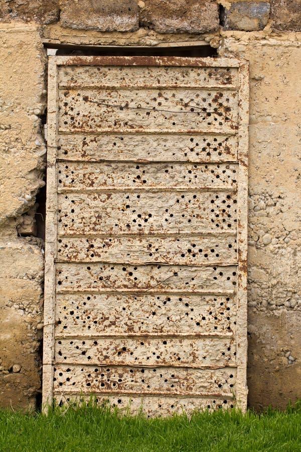Старая ржавая дверь металла в бетонной стене стоковое изображение rf