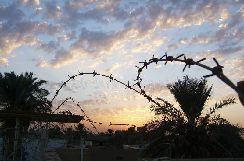 Старая ржавая загородка колючей проволоки безопасностью на голубом небе стоковое фото
