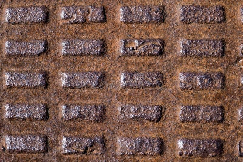 Старая ржавая рифленая крышка люка металла, литое железо с прямоугольниками стоковое изображение rf