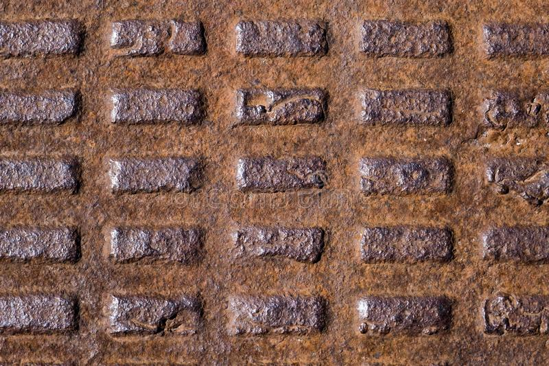 Старая ржавая рифленая крышка люка металла, литое железо с прямоугольниками стоковое фото rf