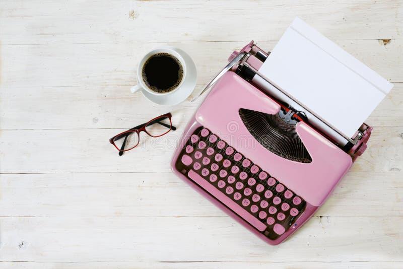 Старая розовая машинка от 1950s с чистым листом бумаги, кофе и стеклами на белой покрашенной деревенской древесине, космосе экзем стоковые фото