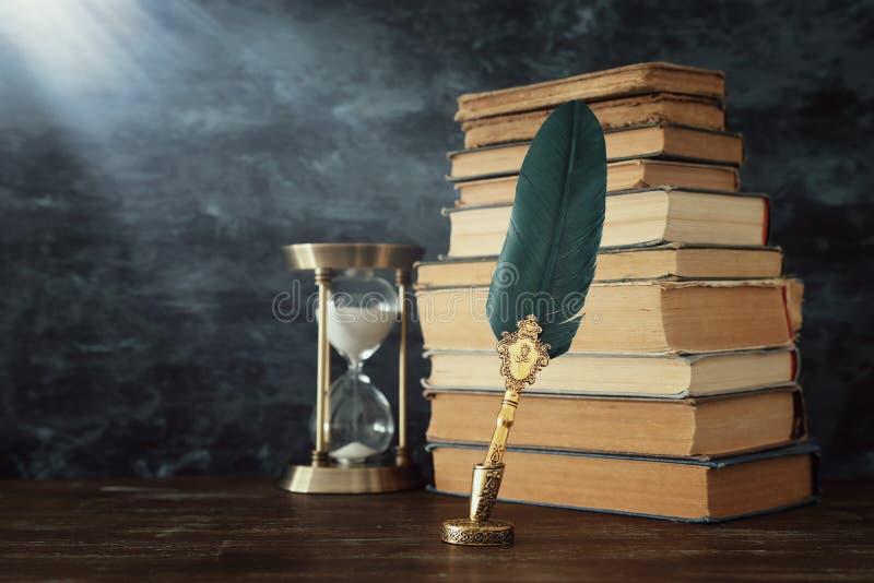 Старая ручка чернил quill пера с чернильницей и старыми книгами над деревянным столом перед черной предпосылкой стены Схематическ стоковое фото