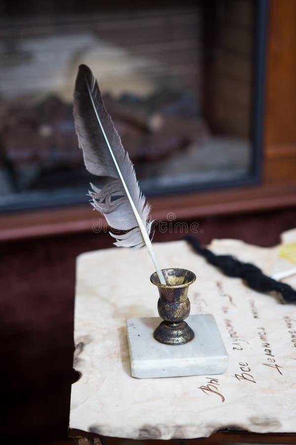 Старая ручка quill, книги и винтажная чернильница на деревянном столе в старом офисе на фоне bookcase и лучи  стоковое фото rf