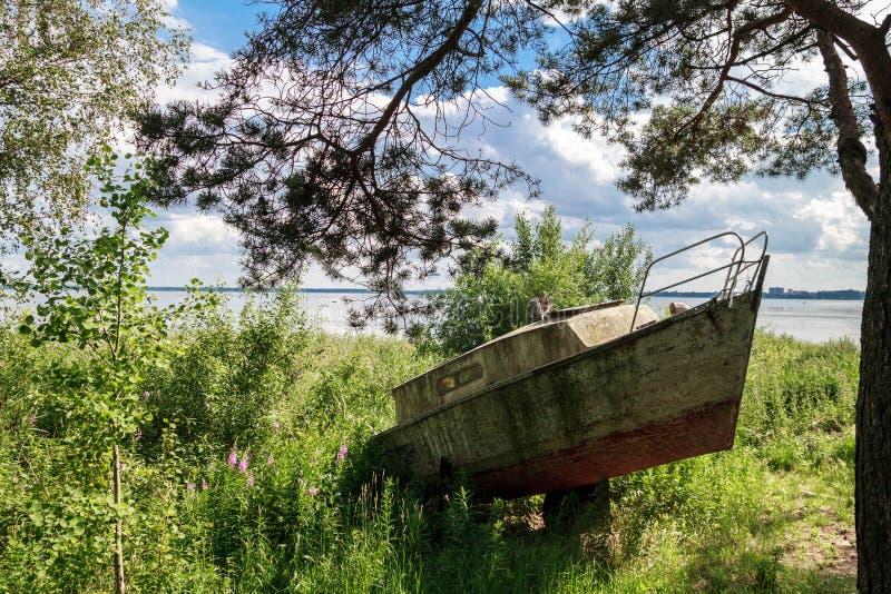 Старая рыбацкая лодка на земле в высокорослой траве покрашенной в красной и сером стоковое фото