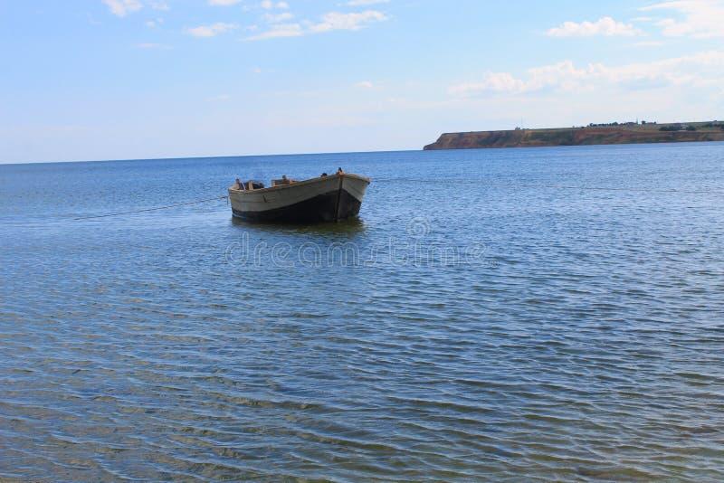Старая рыбацкая лодка на анкере в море около берега песка стоковые изображения