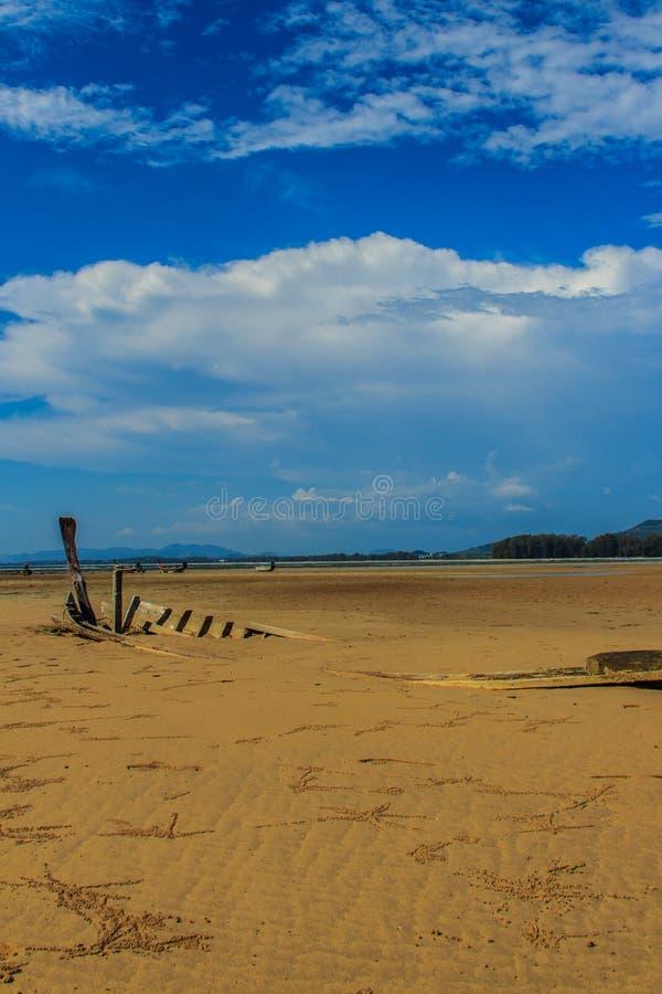 Старая рыбацкая лодка развалины похороненная в песке с голубым небом на облаке стоковое изображение