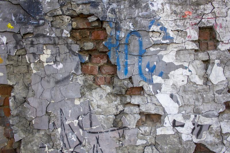 Старая серая тяжело поврежденная бетонная стена с выступая красными кирпичами, отказами и различными пятнами краски Текстура груб стоковые фотографии rf