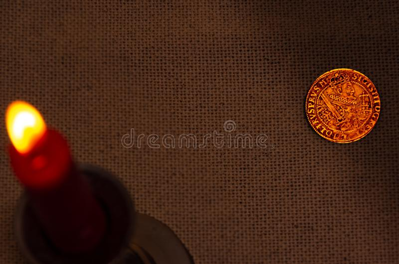 Старая серебряная монета и горя свеча стоковое фото