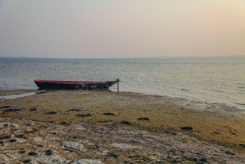 Старая сиротливая рыбацкая лодка стоковое фото