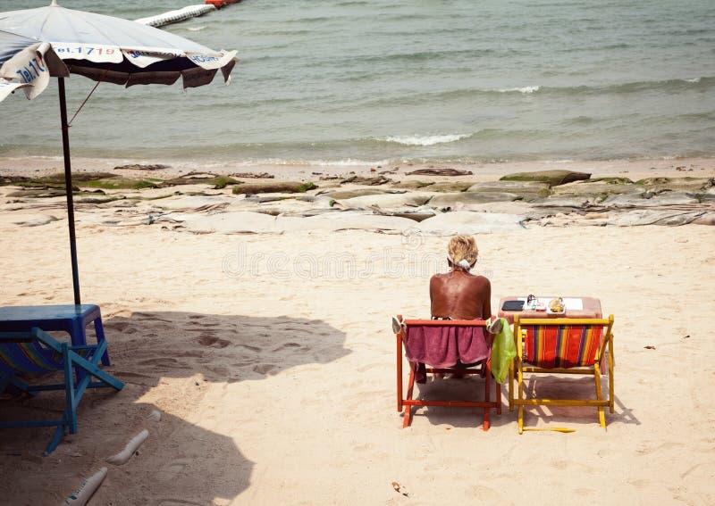 Старая, сиротливая, унылая женщина на пакостном, грязном, солнечном пляже Незадачливое, плохое, сверлильное отключение каникул к  стоковое фото rf