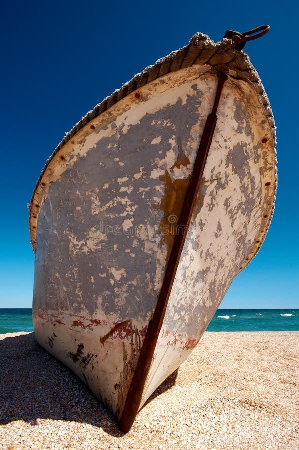 Старая сиротливая шлюпка покинутая на береге моря стоковые фотографии rf