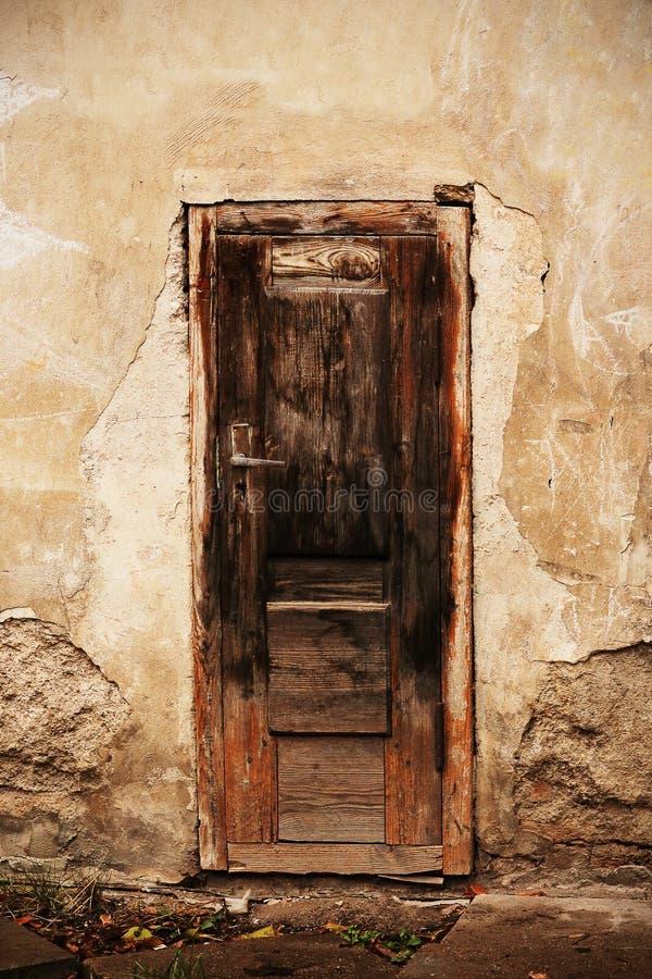 Старая сломанная деревянно-коричневая дверь с высокой рукояткой над землей стоковое изображение
