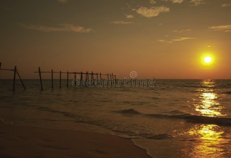 Старая сломленная пристань на пляже на предпосылке захода солнца стоковые изображения rf