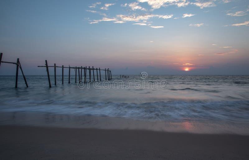 Старая сломленная пристань на пляже на предпосылке захода солнца стоковое изображение