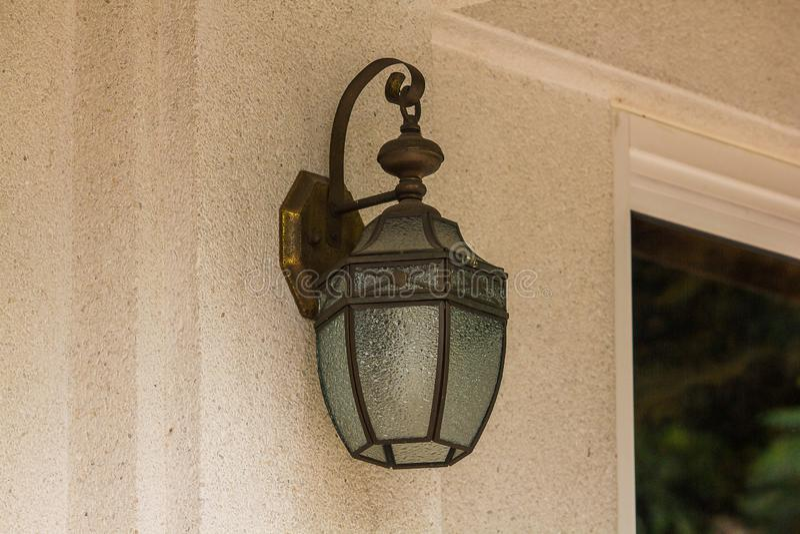 Старая стеклянная лампа на белой стене стоковые фото