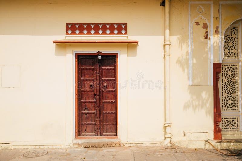 Старая стена и деревянная дверь на дворце города в Джайпуре, Индии стоковые изображения