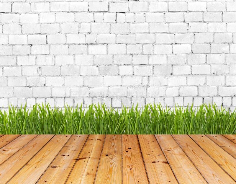 Старая стена и зеленая трава на деревянном поле стоковое фото rf