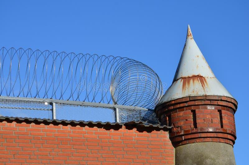 Старая сторожевая башня с barbwire на стене тюрьмы стоковое фото