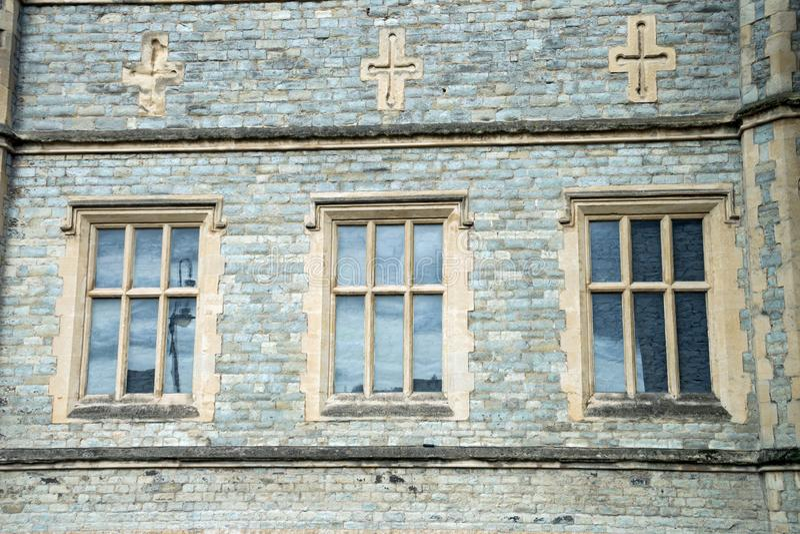 Старая традиционная английская архитектура, 3 окна и кресты выше стоковые изображения rf