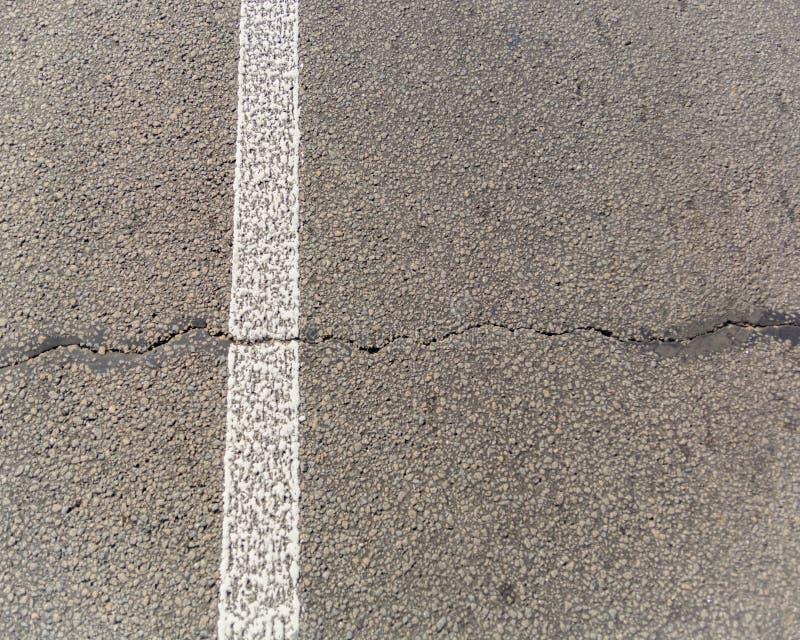 Старая треснутая дорога асфальта Белые маркировки на дороге Отремонтируйте требует скопируйте космос стоковое фото