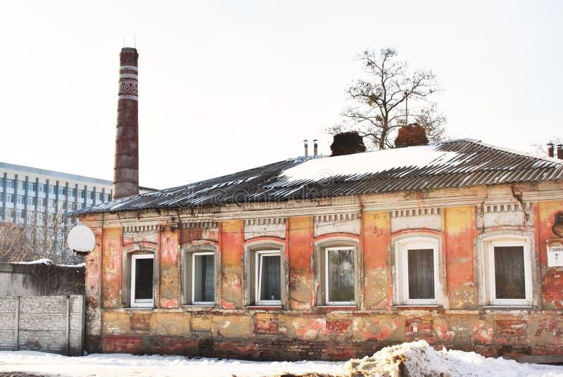 Старая труба красного кирпича с белыми орнаментами, жилым районом с затрапезным розовым домом и административным зданием на предп стоковые изображения