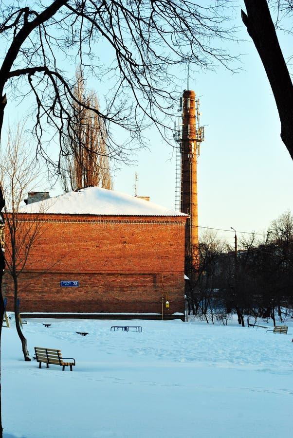 Старая труба красного кирпича с лестницами и платформой замечания, жилым районом с домами, улицей зимы снежной стоковые изображения