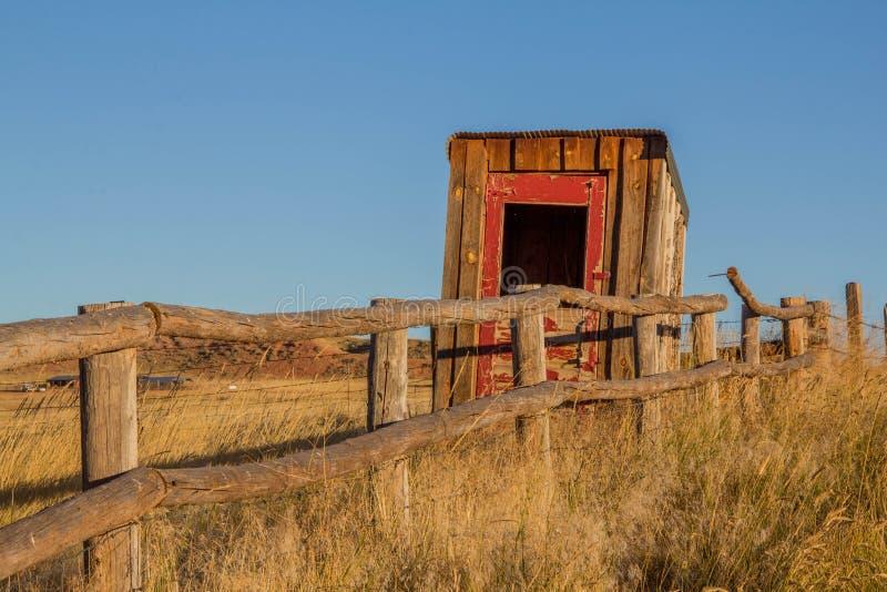 Старая уборная во дворе на ранчо Вайоминга стоковые изображения