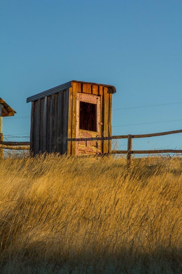 Старая уборная во дворе на ранчо Вайоминга стоковая фотография rf