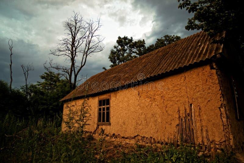 Старая украинская хата грязи дома в деревне на заходе солнца стоковая фотография