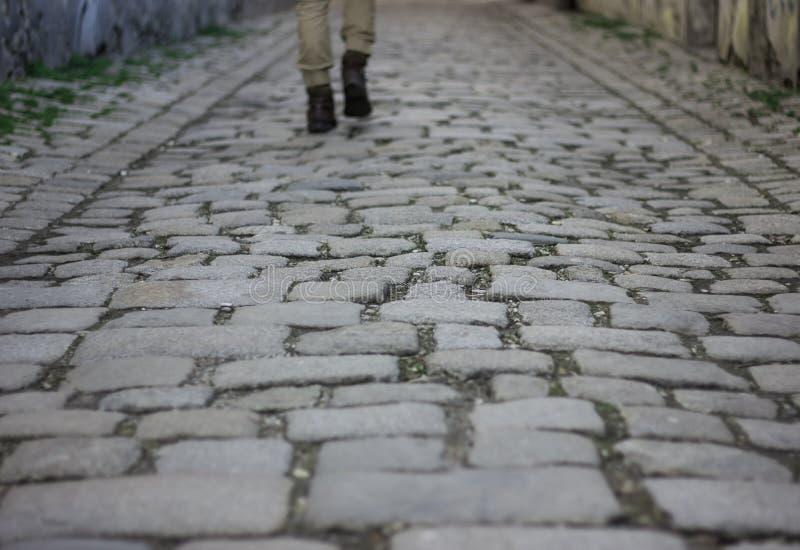 Старая улица макадама с ногами сиротливого ходока как предпосылка стоковые изображения