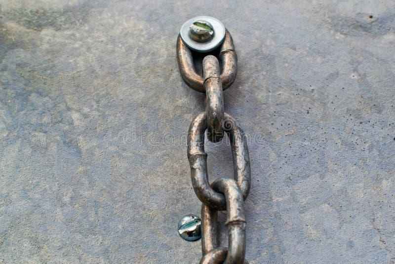 Старая цепь прикрепила болт и шайбу к предпосылке металла стоковая фотография