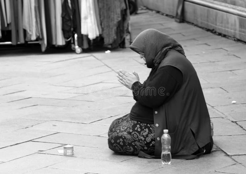 Старая цыганская женщина умоляя на дороге стоковые изображения