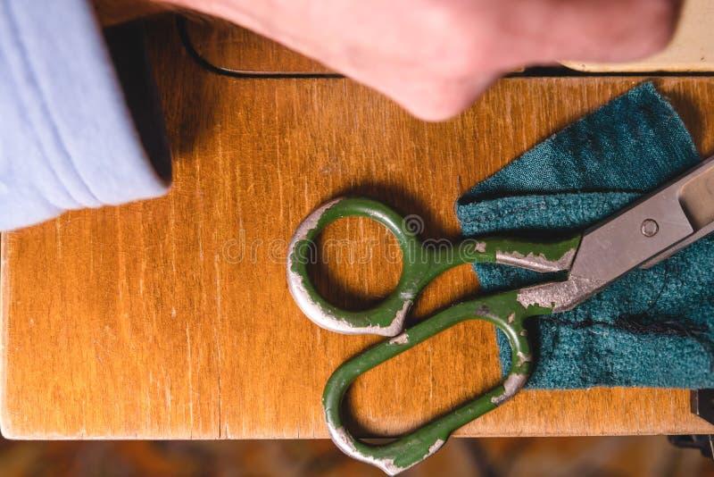 Старая швейная машина с ножницами, на старой grungy таблице работы Таблица работы ` s портноя ткань или точный делать ткани промы стоковая фотография