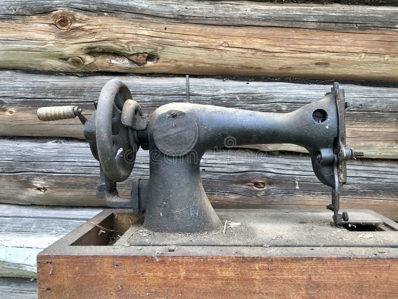 Старая швейная машина, с ручным приводом Покрытый с корозией, пылью и паутинами На фоне деревянного покинутого амбара стоковое фото