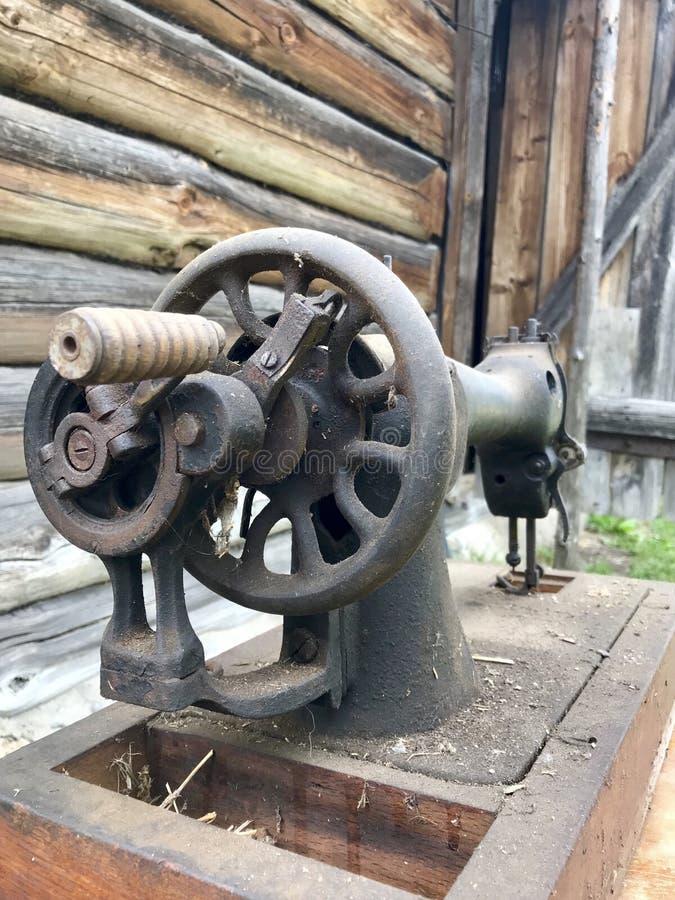 Старая швейная машина, с ручным приводом Покрытый с корозией, пылью и паутинами На фоне деревянного покинутого амбара стоковое изображение rf