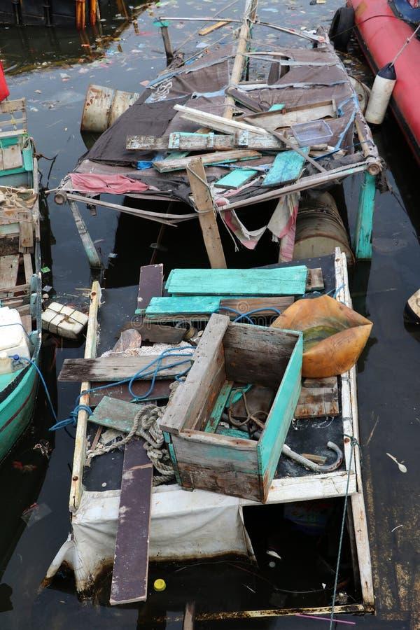 Старая шлюпка разрушенная в море, оно не доступное потому что утечка шлюпки стоковые фото