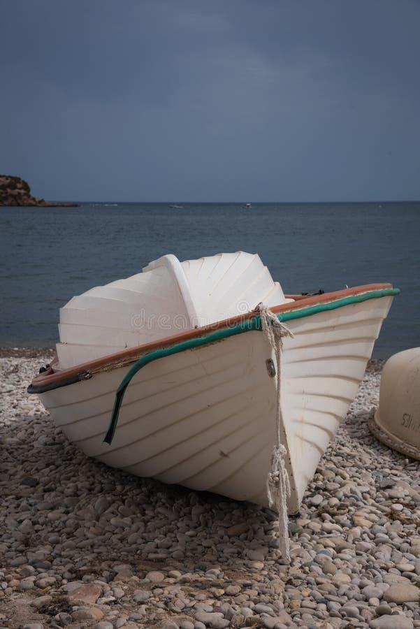 Старая шлюпка на каменном пляже Altea Испании стоковые изображения