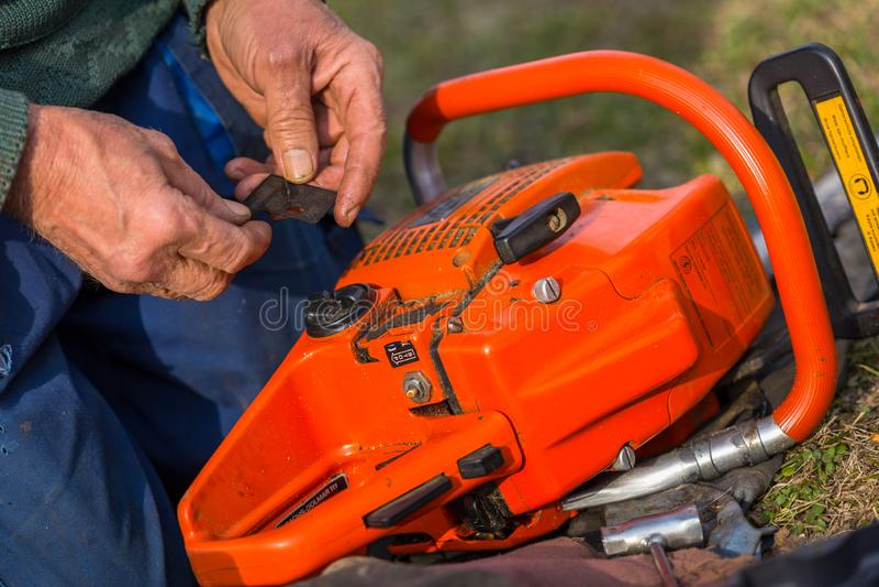 Старик в голубых брюках ремонтирует оранжевую цепную пилу помещенную на том основании с его голыми руками стоковое фото rf