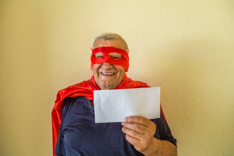 Старик в костюме супергероя держа конверт стоковые фотографии rf