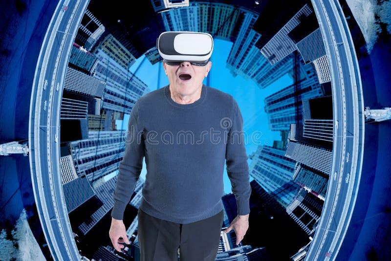 Старик в шлемофоне VR против предпосылки зданий города стоковые фотографии rf