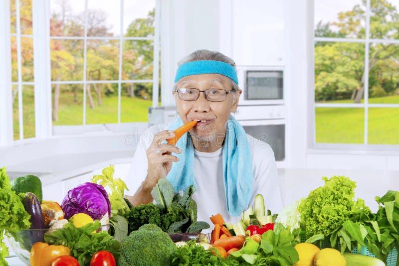 Старик есть морковь в кухне стоковое изображение